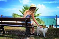 Молодое красивое усаживание девушки и ослабляет на стенде с белым ленивым котом Стоковые Изображения