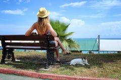 Молодое красивое усаживание девушки и ослабляет на стенде с белым ленивым котом Стоковые Изображения RF