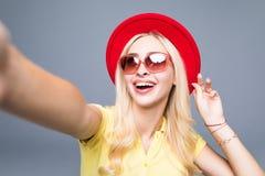 Молодое красивое selfie взятия женщины моды от рук знонит по телефону на серой предпосылке Стоковое Изображение RF