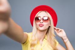 Молодое красивое selfie взятия женщины моды от рук знонит по телефону на серой предпосылке Стоковые Фото
