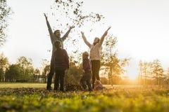 Молодое ликование семьи в восходе солнца осени стоковые фотографии rf