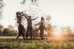 Молодое ликование семьи в пастбище захода солнца осени стоя бросая стоковое изображение rf