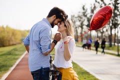 Молодое любящее датировка пар пока ехать bicycles в городе стоковое изображение