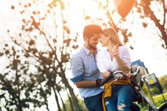 Молодое любящее датировка пар пока ехать bicycles в городе стоковые изображения