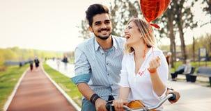 Молодое любящее датировка пар пока ехать bicycles в городе стоковое фото