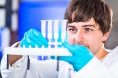 Молодое мужское научное исследование приведения в исполнение исследователя в лаборатории стоковая фотография