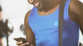 Молодое мужское положение в спортзале с сумкой на плече, сообщении чтения на мобильном телефоне видеоматериал