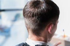 Молодое мужское усаживание на салоне красоты Стрижка человека сфокусируйте мягко стоковые изображения