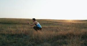 Молодое мужское athlet практикуя длиной поскакать Красная эпопея Человек по пересеченной местностей побежали следом, который скач сток-видео