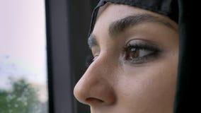 Молодое мусульманское ` s женщины в глазах hijab наблюдает в ненастном окне в шине, концепции погоды, концепции перехода, городск видеоматериал