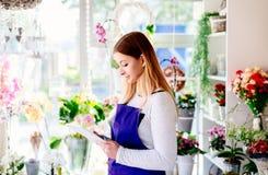 Молодое предприниматель цветочного магазина принимая заказы онлайн таблеткой стоковое изображение rf