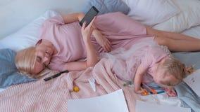 Молодое привлекательное белокурое положение мамы на кровати с ее маленькой очаровательной дочерью в платьях и мобильном телефоне  акции видеоматериалы