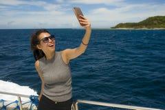 Молодое привлекательное и счастливое азиатское китайское изображение портрета selfie женщины с мобильным телефоном на шлюпке или  Стоковое Изображение RF