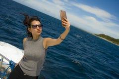 Молодое привлекательное и счастливое азиатское китайское изображение портрета selfie женщины с мобильным телефоном на шлюпке или  Стоковое Фото