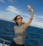 Молодое привлекательное и счастливое азиатское китайское изображение портрета selfie женщины с мобильным телефоном на шлюпке или  Стоковые Фото