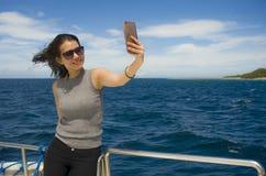 Молодое привлекательное и счастливое азиатское китайское изображение портрета selfie женщины с мобильным телефоном на шлюпке или  Стоковая Фотография RF
