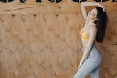 Молодое привлекательное положение девушки фитнеса около окна на предпосылке деревянной стены, отдыхая на занятиях йогой стоковые изображения