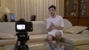 Молодое социальное influencer средств массовой информации снимая новый эпизод на его видео- блоге с камерой дома на кресле - акции видеоматериалы