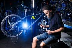 Молодое стильное бородатое, с работником механика длинных волос кавказским мужским на мастерской велосипеда использует инструмент стоковое фото rf