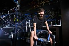 Молодое стильное бородатое, с работником механика длинных волос кавказским мужским на мастерской велосипеда использует инструмент стоковые изображения rf