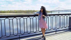 Молодое стильное брюнет положило солнечные очки на сторону и наслаждается красивым взглядом реки сток-видео