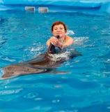 Молодое счастливое заплывание девушки с дельфином стоковая фотография rf