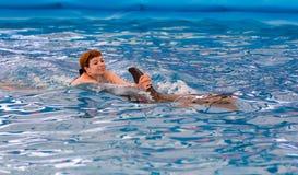 Молодое счастливое заплывание девушки с дельфином стоковое фото