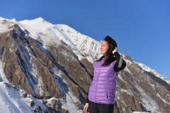 Молодое счастливое положение женщины усмехаясь в снежных горах стоковое фото