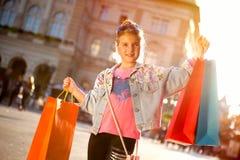 Молодое счастливое современное gir имея потеху с хозяйственными сумками на streeet Стоковые Изображения RF