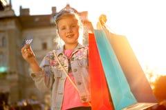 Молодое счастливое современное gir имея потеху с хозяйственными сумками на streeet Стоковая Фотография