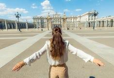 Молодое туристское ликование женщины против королевского дворца стоковые фото