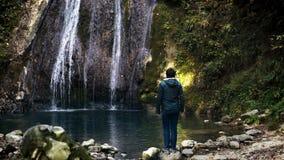 Молодое туристское смотрящ водопад в благоговении видеоматериал
