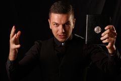 Молодое удерживание священника и секретная библия с логотипом bitcoin стоковое фото rf