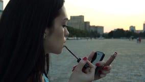 Молодое шикарное брюнет стоит в губной помаде губ улицы и краски видеоматериал