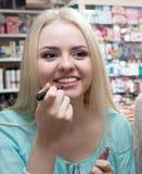 Молодое blondie выбирая лоск губы стоковая фотография