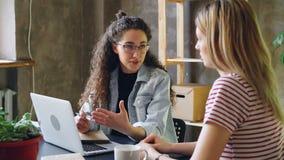 Молодое enterpreneur говорит к ее партнеру в современном офисе пока сидящ на столе совместно Женщины планировать новый акции видеоматериалы