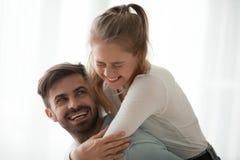 Молодое ouple обнимая дома и смеясь стоковая фотография