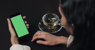 Молодое smarthpone пользы коммерсантки с greenscreen сенсорная панель и конец показывать жестами вверх в кафе Удерживание девушки акции видеоматериалы