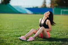 Молодое sporty радостное брюнет женщины в платье спорта сидя на стадионе футбольного поля травы и слушает к музыке в наушниках, h стоковое фото rf