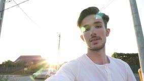 Молодое vlogger принимая камеру от земли идя и говоря пока записывая видео- снаружи, который нужно вывесить его на его блоге - сток-видео