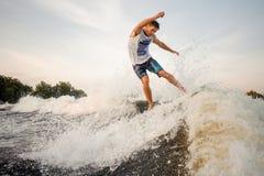 Молодое wakesurfer скача и ехать вниз с реки на борту Стоковые Изображения RF