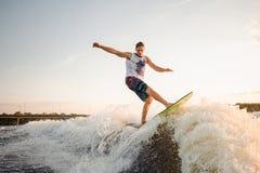 Молодое wakesurfer скача на ехать вниз с реки развевает Стоковое Изображение