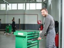 Молодой автоматический механик принимает инструмент от большого и резцовой коробки indoors стоковые изображения rf