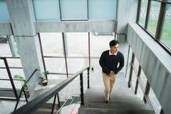 Молодой азиатский бизнесмен вверх по лестницам наслаждается ситуацией стоковые фото