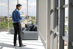 Молодой азиатский бизнесмен держа smartphone стоя около высокорослого стоковое изображение