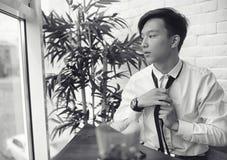 Молодой азиатский бизнесмен ждет партнера в кафе Бушель стоковое фото rf