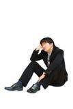 Молодой азиатский бизнесмен сидя и смотря вверх над его головкой стоковое фото