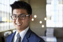 Молодой азиатский бизнесмен усмехаясь к камере, головы и плечи стоковая фотография rf