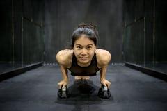 Молодой азиатский делать женщины спортсмена нажимает вверх на поле Стоковые Фото