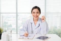 Молодой азиатский женский доктор сидя на таблице и работая на ho Стоковое Изображение RF